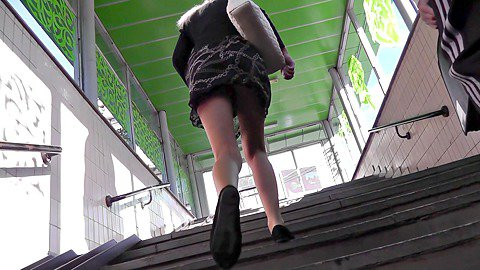 Girl in short skirt hurries up on stairs